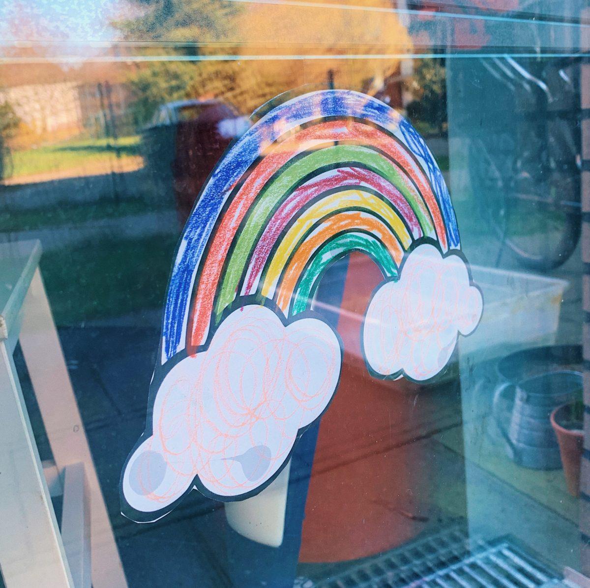 Ein bunter Regenbogen an einem Fenster, Symbol für Kinder die zu Hause bleiben.