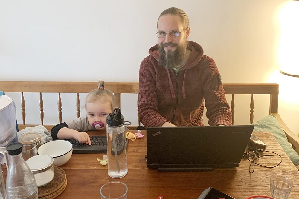 Ein Kind und ein Mann mit Laptop am Esstisch