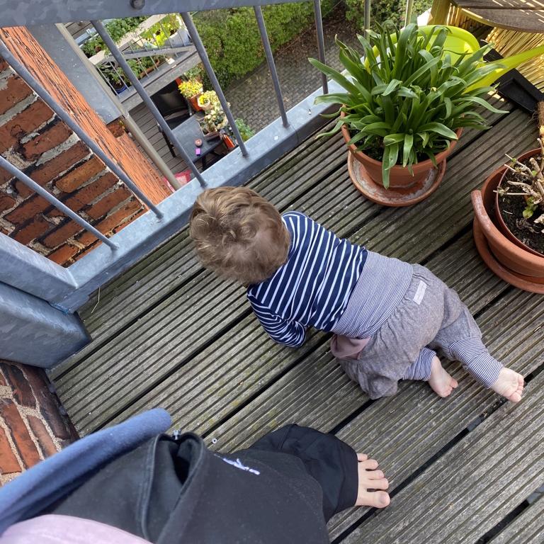 Ein Kleinkind krabbelt auf dem Balkon. Im Bildrand sind Grünpflanzen zu sehen, sowie die Beine einer Person in Jogginghose.
