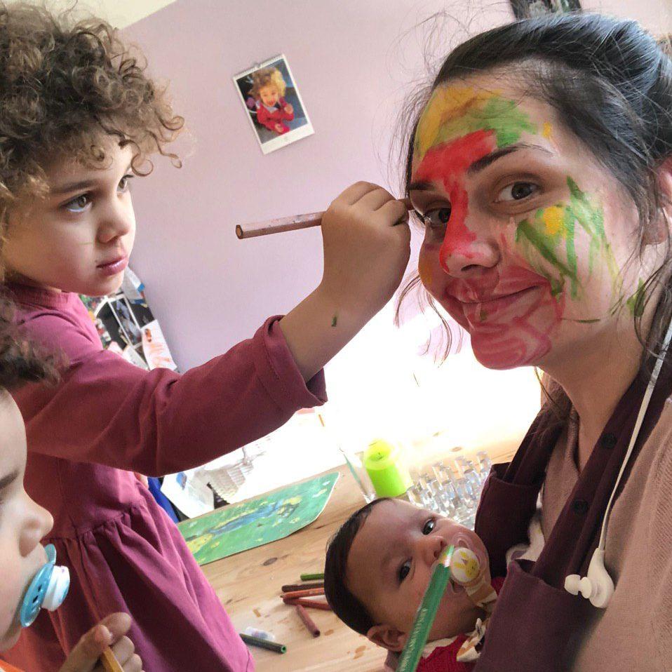Eine Mutter mit einem Baby in der Trage wird von ihren beiden anderen Kindern mit Stiften bunt im Gesicht angemalt.